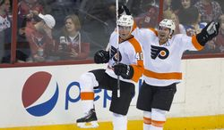 Philadelphia Flyers center Vincent Lecavalier, left, celebrates his game-winning goal with defenseman Kimmo Timonen during overtime of an NHL hockey game against the Washington Capitals on Sunday, March 2, 2014, in Washington. The Flyers defeated the Capitals 5-4. (AP Photo/ Evan Vucci)