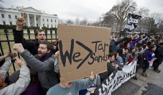 Demonstrators who are strapped to the White House fence in Washington, chant during a protest against the proposed Keystone XL oil pipeline, Sunday, March 2, 2014. They were later arrested. (AP Photo/Manuel Balce Ceneta)