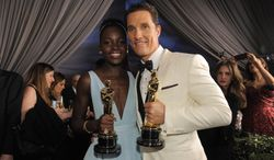 """Lupita Nyong'o, winner of the award for best actress in a supporting role for """"12 Years a Slave"""" and Matthew McConaughey winner of the award for best actor for his role in the """"Dallas Buyers Club"""" attend the Governors Ball after the Oscars on Sunday, March 2, 2014, at the Dolby Theatre in Los Angeles.  (Photo by Chris Pizzello/Invision/AP)"""