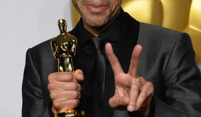 "John Ridley poses in the press room with the award for best adapted screenplay of the year for ""12 Years a Slave"" during the Oscars at the Dolby Theatre on Sunday, March 2, 2014, in Los Angeles.  (Photo by Jordan Strauss/Invision/AP)"