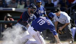Cleveland Indians catcher Luke Carlin, tags Texas Rangers' Mitch Moreland (18) as home plate umpire David Rackley, right, watches in the fourth inning of a spring training exhibition baseball game, Monday, March 3, 2014, in Surprise , Ariz. Moreland was trying to score on a hit by J.P. Arencibia. (AP Photo/Tony Gutierrez)