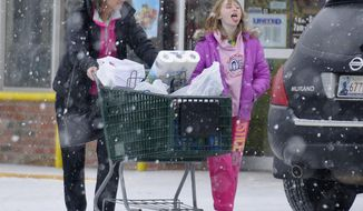 A girl tries to catch a snowflake on her tougue as she leaves a supermarket with her mother, Sunday, March 2, 2014, in Enid, Okla. (AP Photo/The Enid News & Eagle, Billy Hefton)