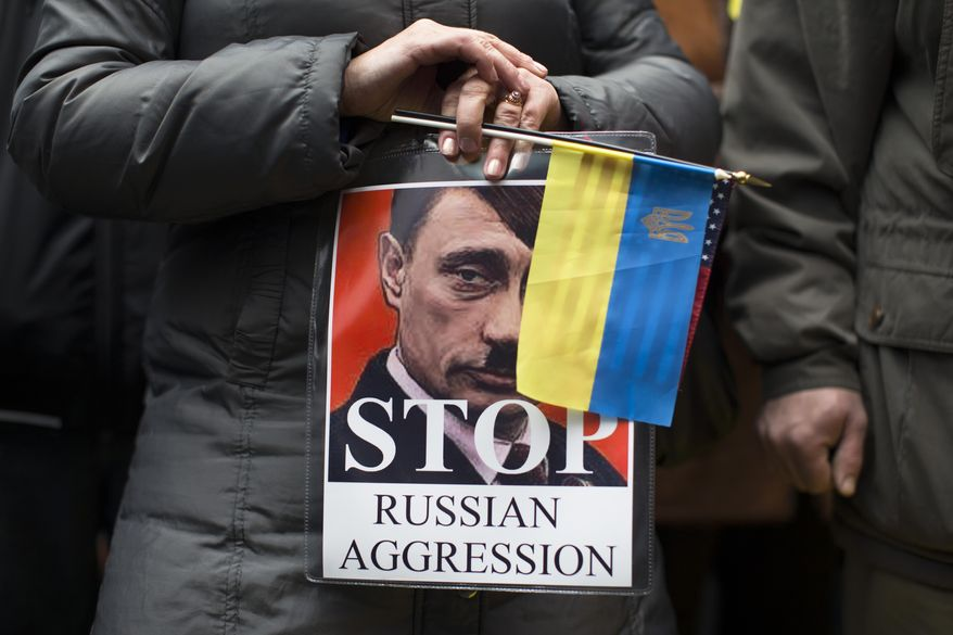 "Demonstrators against Russian military actions in Ukraine rally in Times Square, Sunday, March 2, 2014, in New York. Western powers are prepared ""to go to the hilt"" to isolate Russia for its military incursion into Ukraine, ""an incredible act of aggression"" that may lead to visa bans, asset freezes, trade and investment penalties, and a boycott of a Russian-hosted economic summit of global powers in June, Secretary of State John Kerry said Sunday. (AP Photo/John Minchillo)"