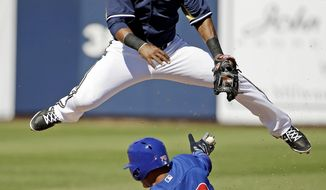 Milwaukee Brewers' Jean Segura leaps over Chicago Cubs' Javier Baez (70) as he tries to turn a double play on a ball hit by Aaron Cunningham during the fourth inning of an exhibition spring training baseball game Monday, March 3, 2014, in Phoenix. Cunningham beat the throw to first. (AP Photo/Morry Gash)