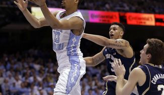 North Carolina's J.P. Tokoto (13) drives to the basket as Notre Dame's Zach Auguste and Pat Connaughton, right, defend during the first half of an NCAA college basketball game in Chapel Hill, N.C., Monday, March 3, 2014. (AP Photo/Gerry Broome)