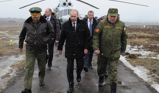 Russian President Vladimir Putin, center, and Defense Minister Sergei Shoigu, left, and the commander of the Western Military District Anatoly Sidorov, right, walk upon arrival to watch military exercise near St.Petersburg, Russia, Monday, March 3, 2014. Putin has sought and quickly got the Russian parliament's permission to use the Russian military in Ukraine.(AP Photo/RIA-Novosti, Mikhail Klimentyev, Presidential Press Service)