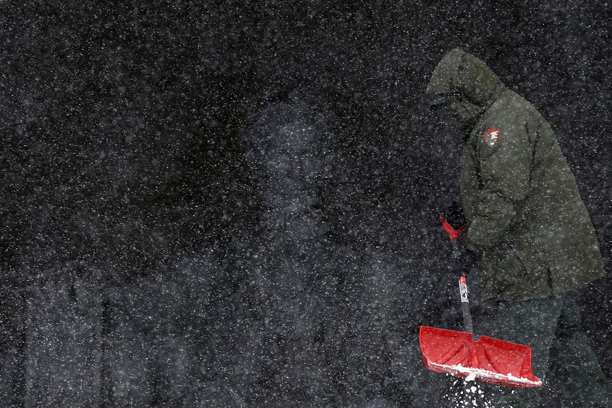 National Park Service employee Eric Tolliver shovels snow and ice at the Lincoln Memorial as snow falls in Washington, Monday, March 3, 2014. The National Weather Service has issued a Winter Storm Warning for the greater Washington Metropolitan region, prompting area schools and the federal government to close for the wintry weather. (AP Photo/Charles Dharapak)