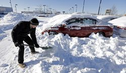 ** FILE ** In this Tuesday, Jan. 7, 2014, file photo, a salesmen at a car dealer digs out cars covered in snow at a dealership in Indianapolis, as temperatures hovered around zero.  The subzero cold followed inches of snow and high winds that made traveling treacherous. (AP Photo/Michael Conroy, File)