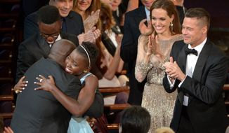 "Director Steve McQueen, left, congratulates Lupita Nyong'o on her win for best actress in a supporting role for ""12 Years a Slave"" as her brother Peter, background from left, and actors John Travolta, Kelly Preston, Benedict Cumberbatch, Angelina Jolie and Brad Pitt, look on, during the Oscars at the Dolby Theatre on Sunday, March 2, 2014, in Los Angeles.  (Photo by John Shearer/Invision/AP)"