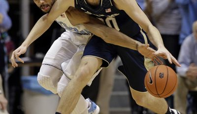 North Carolina's James Michael McAdoo, left, and Notre Dame's Austin Burgett reach for a loose ball during the first half of an NCAA college basketball game in Chapel Hill, N.C., Monday, March 3, 2014. (AP Photo/Gerry Broome)
