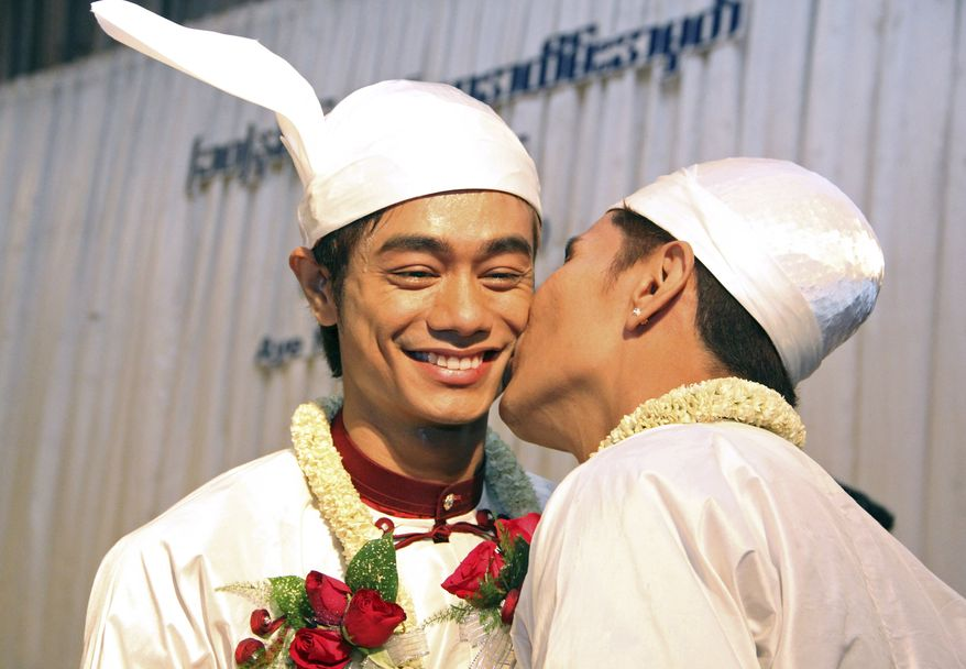 In this March 2, 2014 photo, Myo Min Htet, left, receives kisses from Tin Ko Ko, right, during their wedding reception, at Excel Tower in Yangon, Myanmar.  Ten years after they fell in love and moved in together, Tin Ko Ko, 38, and Myo Min Htet, 28, over the weekend became Myanmar's first gay couple to publicly get married. (AP Photo/Khin Maung Win)