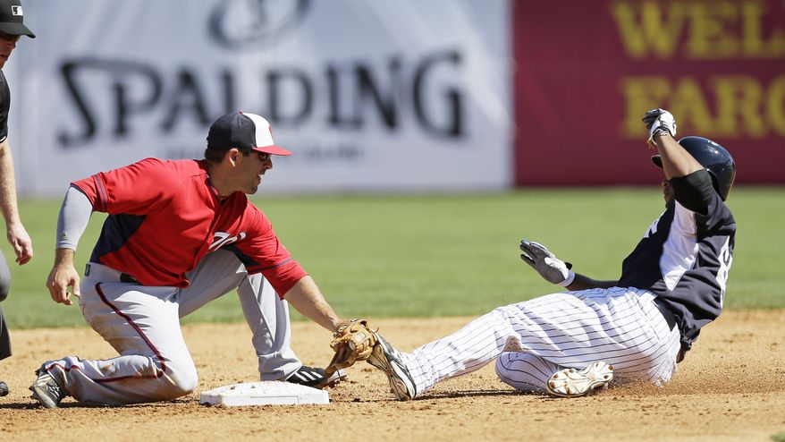 New York Yankees' Zoilo Almonte, right, is tagged out by Washington Nationals second baseman Danny Espinosa while trying for a double during the fourth inning of an exhibition baseball game Monday, March 3, 2014, in Tampa, Fla. (AP Photo/Charlie Neibergall)