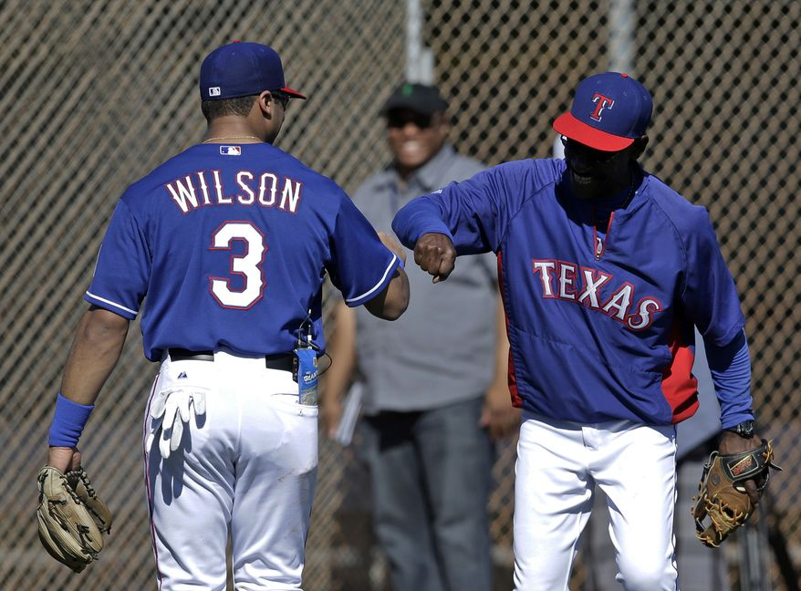 Seattle Seahawks quarterback Russell Wilson gets a little fist bump from Texas Rangers manager Ron Washington, right, as the two joke around on the practice field during spring training baseball practice, Monday, March 3, 2014, in Surprise, Ariz. (AP Photo/Tony Gutierrez)