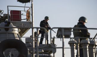 Ukrainian seamen stand guard on the Ukrainian navy ship Slavutich at harbor of  Sevastopol, Ukraine, Monday, March 3, 2014. The Ukrainian Defense Ministry said that Russian forces that have overtaken Ukraine's strategic region of Crimea are demanding that the ship's crew surrender.  (AP Photo/Andrew Lubimov)