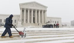 A workman clears snow from the plaza at the U.S. Supreme Court in Washington in Washington, Monday, March 3, 2014, as visitors line up to hear arguments. The National Weather Service has issued a Winter Storm Warning for the greater Washington Metropolitan region, prompting area schools and the federal government to close for the wintry weather.  (AP Photo/J. Scott Applewhite)