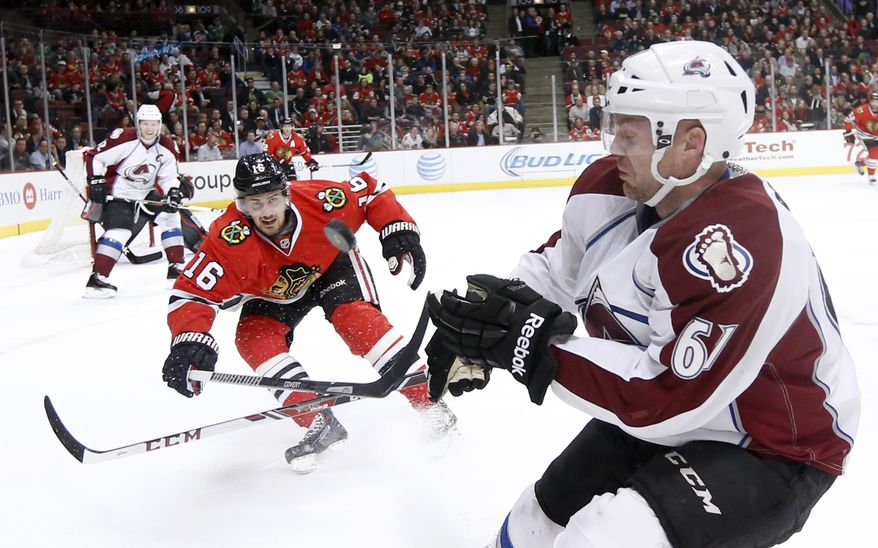 Chicago Blackhawks center Marcus Kruger (16) and Colorado Avalanche defenseman Andre Benoit (61) battle for a loose puck during the first period of an NHL hockey game Tuesday, March 4, 2014, in Chicago. (AP Photo/Charles Rex Arbogast)
