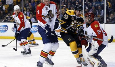 Boston Bruins left wing Brad Marchand (63) fights for position against Florida Panthers defenseman Dylan Olsen (4) and goalie Tim Thomas (34) as the puck squirts away during the second period of an NHL hockey game in Boston, Tuesday, March 4, 2014. (AP Photo/Elise Amendola)