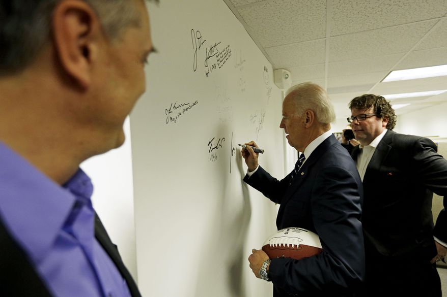 Vice President Joe Biden signs a wall inside the BG Ad Group as the firm's president Darien Southerland, right, looks on during a visit to the Cobb County marketing and advertising agency, Tuesday, March 4, 2014, in Atlanta. (AP Photo/David Goldman, Pool)