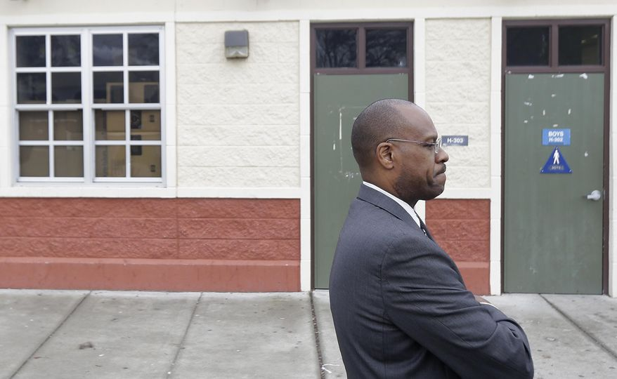 Charles Ramsey, president of the West Contra Costa school board, stands outside of the boys bathroom where police were investigating reports of a brutal assault of a transgender teen at the Hercules Middle-High School campus in Hercules, Calif., Tuesday, March 4, 2014. The 15-year-old student told officers he was leaving a boy's bathroom at Hercules High School on Monday when three teenage boys pushed him inside a handicapped stall and physically and sexually assaulted him, Hercules police Detective Connie Van Putten said. (AP Photo/Jeff Chiu)