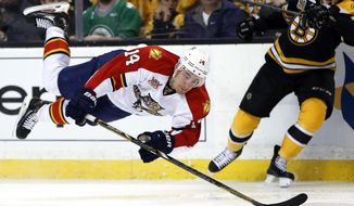Florida Panthers left wing Tomas Fleischmann (14) dives for the puck as Boston Bruins defenseman Kevan Miller (86) watches during the third period of an NHL hockey game in Boston, Tuesday, March 4, 2014. (AP Photo/Elise Amendola)