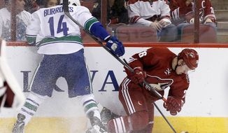 Vancouver Canucks' Alex Burrows (14) sends Phoenix Coyotes' Michael Stone, right, to the ice, but Burrows is called for a penalty, during the first period of an NHL hockey game on Tuesday, March 4, 2014, in Glendale, Ariz. (AP Photo/Ross D. Franklin)