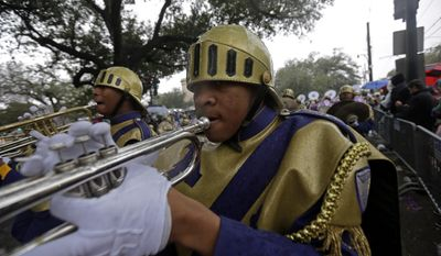 Members of the St. Augustine High Marching 100 band march in the Krewe of Zulu parade during Mardi Gras day in New Orleans, Tuesday, March 4, 2014. The Zulu parade began on schedule, led by a New Orleans police vanguard on horseback that included Mayor Mitch Landrieu.(AP Photo/Gerald Herbert)
