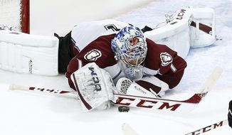 Colorado Avalanche goalie Semyon Varlamov (1) dives on a loose puck during the third period of an NHL hockey game against the Chicago Blackhawks Tuesday, March 4, 2014, in Chicago. The Avalanche won 4-2. (AP Photo/Charles Rex Arbogast)
