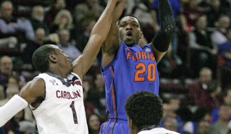 Florida's Michael Frazier (20) hits his field goal as South Carolina's Brenton Williams (1) tries to block during the first half of their NCAA college basketball game Tuesday, March 4, 2014, in Columbia, S.C.(AP Photo/Mary Ann Chastain)
