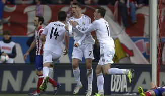 Real's Cristiano Ronaldo, centre, celebrates his goal with teammate Gareth Bale, right, during a Spanish La Liga soccer match between Atletico de Madrid and Real Madrid at the Vicente Calderon stadium in Madrid, Spain, Sunday, March 2, 2014. (AP Photo/Andres Kudacki)