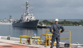 American naval destroyer USS Michael Murphy escorts passengers from a Canadian navy vessel to Pearl Harbor, Hawaii on Tuesday, March 4, 2014. A U.S. Navy ocean tug was towing the Canadian ship after an engine fire left 20 sailors with minor injuries. (AP Photo/Oskar Garcia)