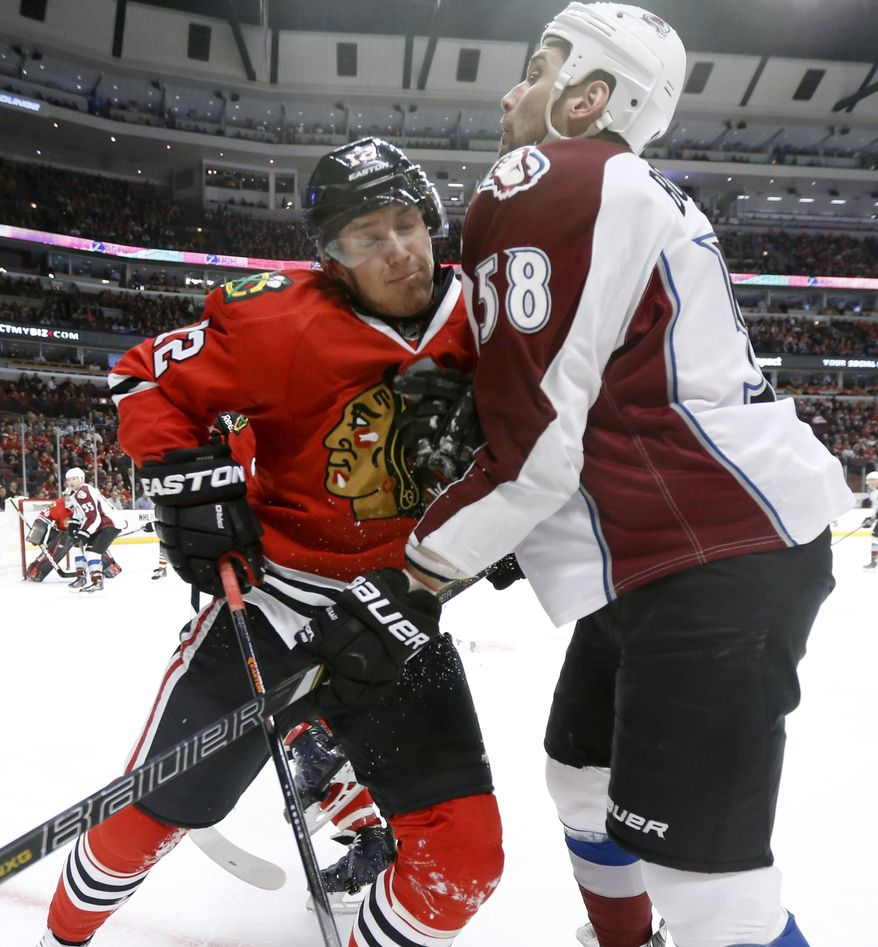 Chicago Blackhawks center Peter Regin (12) and Colorado Avalanche left wing Patrick Bordeleau collide during the first period of an NHL hockey game Tuesday, March 4, 2014, in Chicago. (AP Photo/Charles Rex Arbogast)