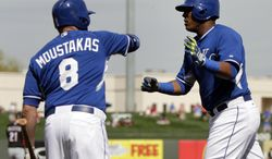 Kansas City Royals' Mike Moustakas (8) congratulates Salvador Perez, right, on his solo home run off Cincinnati Reds' Johnny Cueto in the second inning of a spring training baseball game, Tuesday, March 4, 2014, in Surprise, Ariz. (AP Photo/Tony Gutierrez)