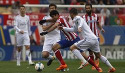 Atletico's Diego Costa, center, in action with Real's Xabi Alonso, left, during a Spanish La Liga soccer match between Atletico de Madrid and Real Madrid at the Vicente Calderon stadium in Madrid, Spain, Sunday, March 2, 2014. (AP Photo/Gabriel Pecot)