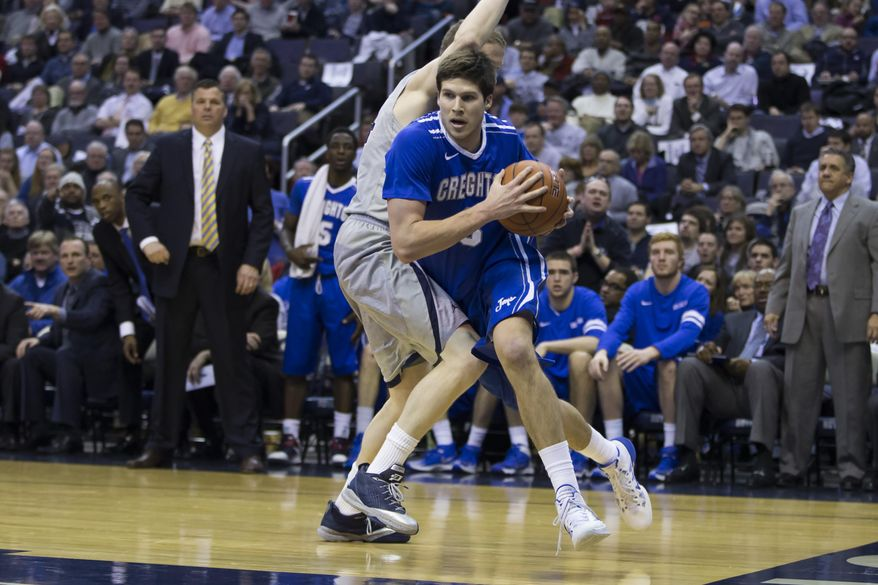 Creighton forward Doug McDermott, right, drives past Georgetown forward Nate Lubick during the second half of an NCAA basketball game on Tuesday, March 4, 2014, in Washington. Georgetown defeated Creighton 75-63. (AP Photo/ Evan Vucci)
