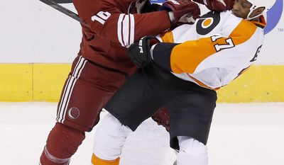 Phoenix Coyotes' Rostislav Klesla (16), of the Czech Republic, checks Philadelphia Flyers' Wayne Simmonds (17) to the ice during the first period of an NHL hockey game Saturday, Jan. 4, 2014, in Glendale, Ariz. (AP Photo/Ross D. Franklin)