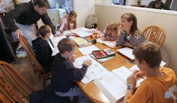FILE -- This March 13, 2009, file photo shows Uwe Romeike, top left, and his wife Hannelore, second from right, teaching their children at their home in Morristown, Tenn. An attorney for a German couple who lost their bid for U.S. asylum in order to home-school their seven children says deportation proceedings against the family have been deferred indefinitely, Tuesday, March 4, 2014.  (AP Photo/Wade Payne, File)