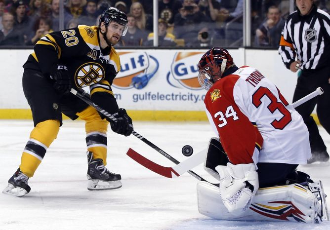 Florida Panthers goalie Tim Thomas (34) makes the save on a breakaway attempt by Boston Bruins left wing Daniel Paille (20) during the second period of an NHL hockey game in Boston, Tuesday, March 4, 2014. (AP Photo/Elise Amendola)