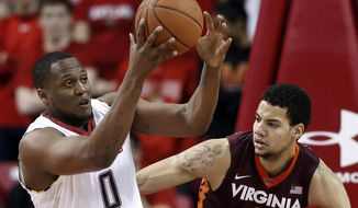 Maryland forward Charles Mitchell, left, tries to hold on to a rebound in front of Virginia Tech forward Joey Van Zegeren during the first half of an NCAA college basketball game in College Park, Md., Tuesday, March 4, 2014. (AP Photo/Patrick Semansky)