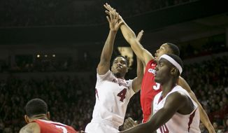 Arkansas guard Coty Clarke (4) shoots a jump shot over a group of Georgia defenders during the second half of an NCAA college basketball game on Saturday, March 1, 2014, in Fayetteville, Ark.. Clarke led the Razorbacks in scoring with 23 points as Arkansas defeated 87-75. (AP Photo/Gareth Patterson)