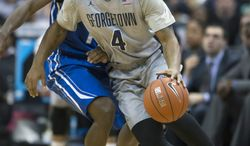 Georgetown guard D'Vauntes Smith-Rivera (4) drives past Creighton guard Austin Chatman during the second half of an NCAA basketball game on Tuesday, March 4, 2014, in Washington. Georgetown defeated Creighton 75-63. (AP Photo/ Evan Vucci)
