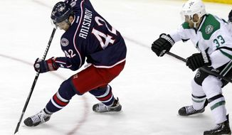 Columbus Blue Jackets' Artem Anisimov, left, of Russia, settles the puck in front of Dallas Stars' Alex Goligoski in the third period of an NHL hockey game in Columbus, Ohio, Tuesday, March 4, 2014. Anisimov scored on the play. Columbus won 4-2. (AP Photo/Paul Vernon)