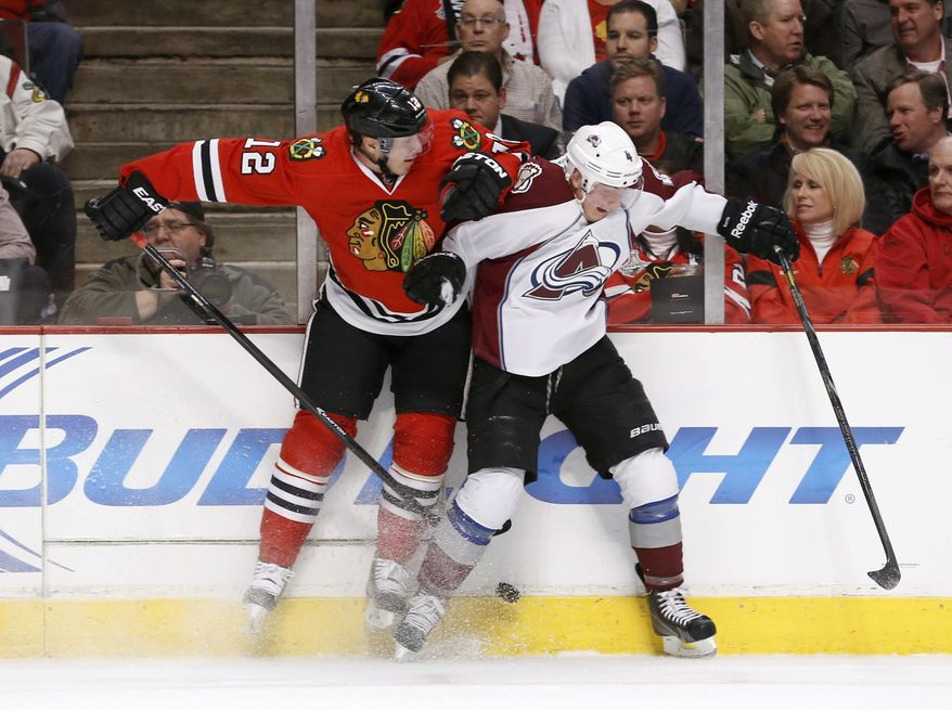 Chicago Blackhawks center Peter Regin (12) checks Colorado Avalanche defenseman Tyson Barrie (4) along the boards during the first period of an NHL hockey game Tuesday, March 4, 2014, in Chicago. (AP Photo/Charles Rex Arbogast)