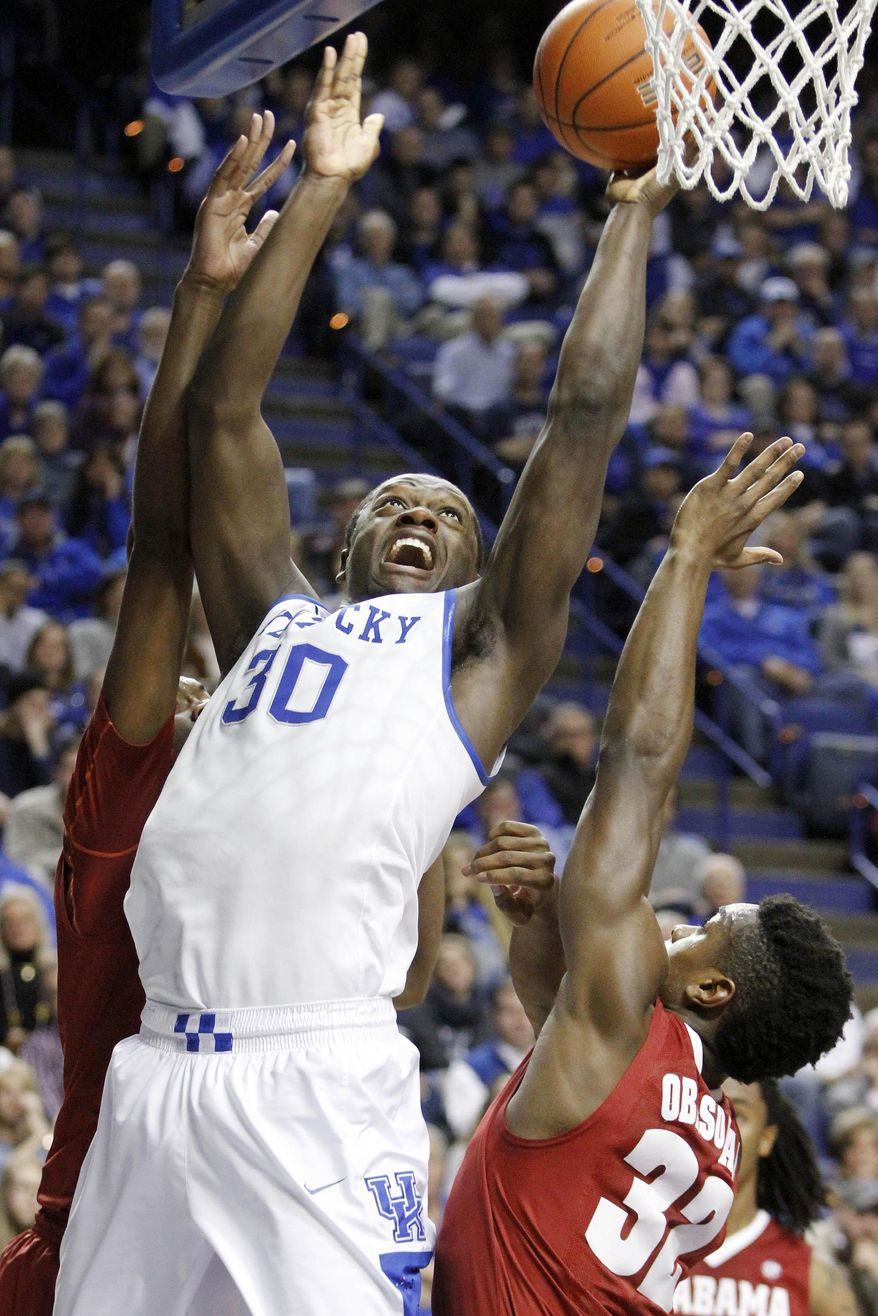 Kentucky's Julius Randle (30) shoots under pressure from Alabama's Jimmie Taylor, left, and Retin Obasohan (32) during the first half of an NCAA college basketball game, Tuesday, March 4, 2014, in Lexington, Ky. (AP Photo/James Crisp)