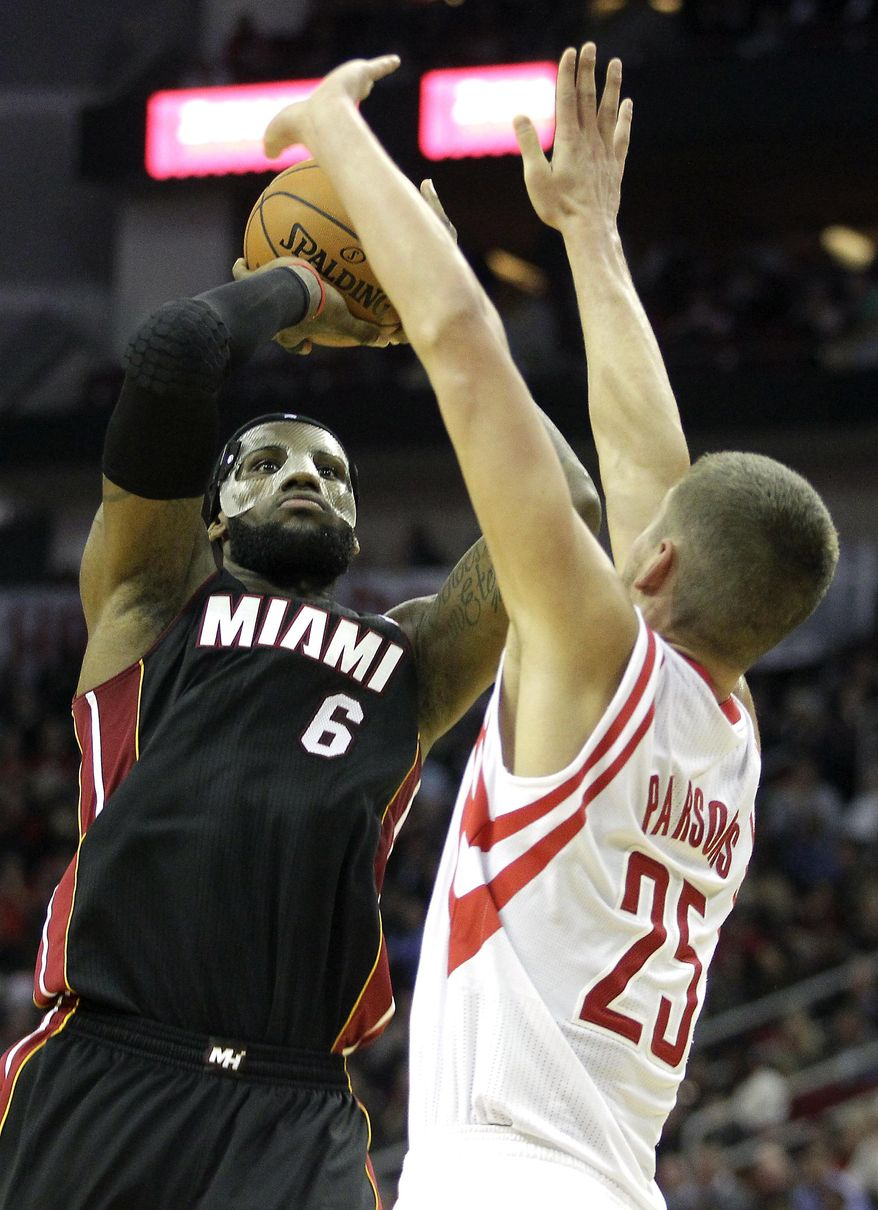 Miami Heat forward LeBron James (6) takes a shot over Houston Rockets forward Chandler Parsons (25) during the second quarter of an NBA basketball game, Tuesday, March. 4, 2014, in Houston. (AP Photo/Patric Schneider)