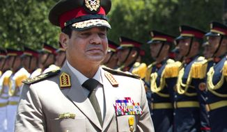 """FILE - In this Wednesday, April 24, 2013 file photo, Egyptian Defense Minister Gen. Abdel-Fattah el-Sissi reviews honor guards during an arrival ceremony for his U.S. counterpart at the Ministry of Defense in Cairo. Egypt's military chief says he """"can't turn his back"""" if the majority of Egyptians want him to run for president. El-Sissi's comments, made in a speech Tuesday, March 4, 2014 to military cadets and reported by the state news agency MEAN, are his strongest yet suggesting he intends to run. (AP Photo/Jim Watson, Pool, File)"""