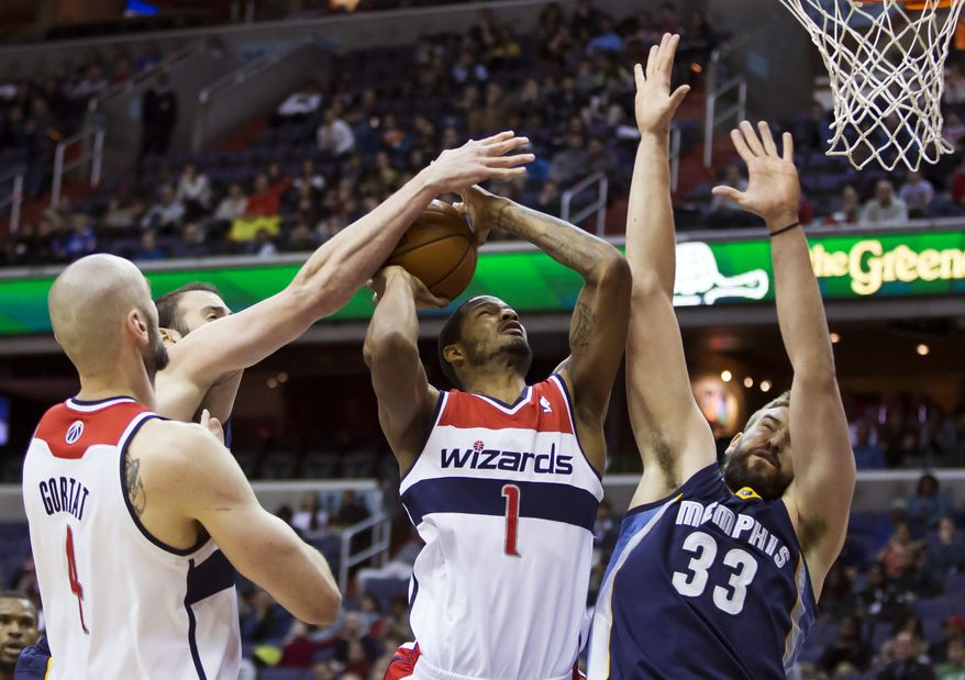 Washington Wizards forward Trevor Ariza (1) is defended by Memphis Grizzlies center Marc Gasol (33) and Memphis Grizzlies center Kosta Koufos during the second half of an NBA basketball game on Monday, March 3, 2014, in Washington. The Grizzlies won 110-104. At left is Washington Wizards center Marcin Gortat. (AP Photo/ Evan Vucci)