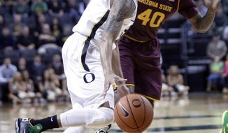 Oregon guard Joseph Young, left, drives to the basket past Arizona State forward Shaquielle McKissic during the first half of an NCAA college basketball game in Eugene, Ore., Tuesday, March 4, 2014. (AP Photo/Don Ryan)