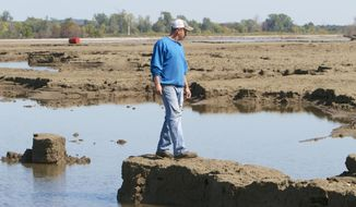 In this photo from Sept. 19, 2011, Rob Chatt surveys damage from the Missouri River flooding to his family farm in Tekamah, Neb. A group of farmers and business owners sued the U.S. Army Corps of Engineers on Wednesday, March 5, 2014, seeking compensation for claims the agency mismanaged the Missouri River since 2006 and contributed to major flooding in five states. The federal lawsuit claims some plaintiffs experienced extensive damage, particularly during the extended 2011 flooding that devastated hundreds of thousands of acres of mostly farmland in South Dakota, Nebraska, Iowa, Kansas and Missouri. (AP Photo/Nati Harnik)