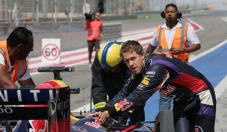 Formula One driver Sebastian Vettel of Red Bull Racing helps push his car after breaking down during pre-season testing at the Bahrain International Circuit in Sakhir, Bahrain, Saturday, March 1, 2014. (AP Photo/Hasan Jamali)