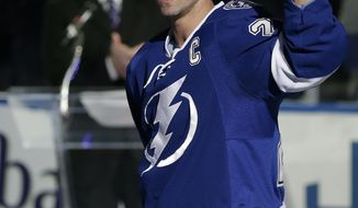 FILE - In this Nov. 25, 2013 file photo, Tampa Bay Lightning right wing Martin St. Louis (26) waves to the fans during a celebration of his 1,000th game before an NHL hockey game against the New York Rangers, in Tampa, Fla. The New York Rangers and Tampa Bay Lightning are pulling off the first major deal on NHL trade deadline day, Wednesday, March 5, 2014, swapping captains Ryan Callahan and Martin St. Louis.(AP Photo/Chris O'Meara, File)